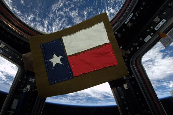 Simply made.  In space.  A memento for my husband, made with pieces cut from t-shirts I wore during my stay on Space Station, stitched lightly onto a Russian food container liner.  We met in Texas, got married in Texas and had our son in Texas.  A special place!  KN from space.