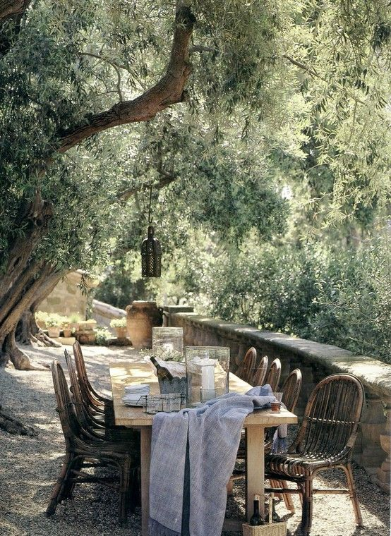 Outdoor dining table and rattan bistro chairs in the countryside..Romantic French Country Garden Courtyard Ideas. #frenchcountry #provence #outdoordining #garden #courtyard