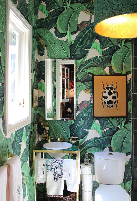 the mixed malachite accents + emerald palm wallpaper bring this bathroom to life:
