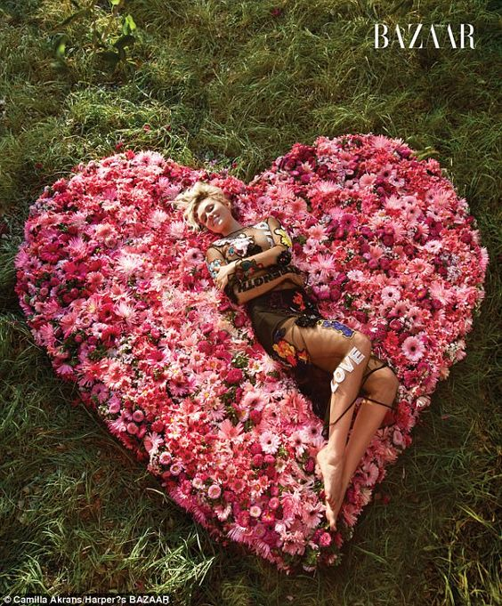 Flower power: The blonde poses on a heart-shaped flower bed in a statement shirt and match...