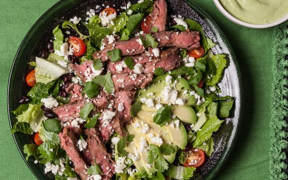 A healthy Mexican grilled flank steak recipe. You will need romaine lettuce, canned black beans, cherry tomatoes, avocado, queso fresco, and cilantro.