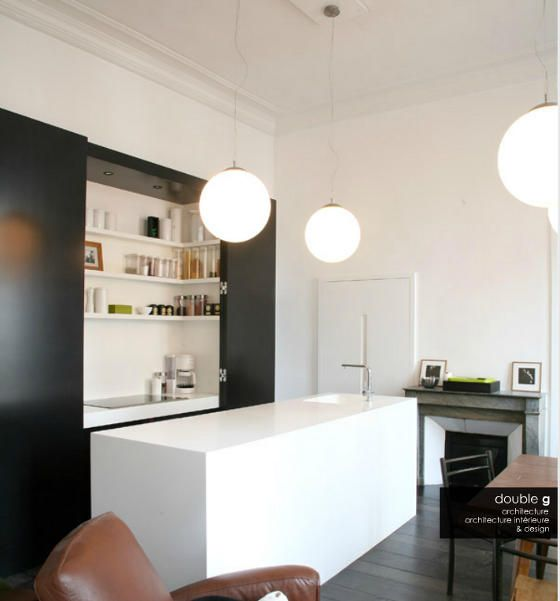 A sleek, almost sculptural solution to open plan living with kitchen in plain view. Hide it way but celebrate the deception. Love this little black and white kitchen by double g.