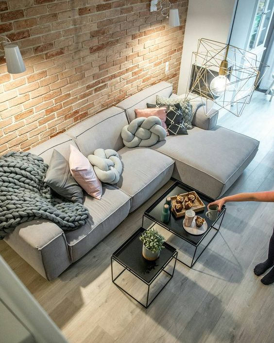 Sala de estar com parede de tijolo, sofá cinza e almofadas em tons neutros (cinza, preto e rosa), mesa de centro preto. Piso em madeira claro e luminária pendente.