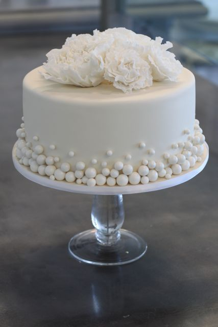 Excellent one to do in smoothed buttercream with buttercream ball border and removable gumpaste flowers. I like this for a wedding cake with the balls the color of the wedding.: