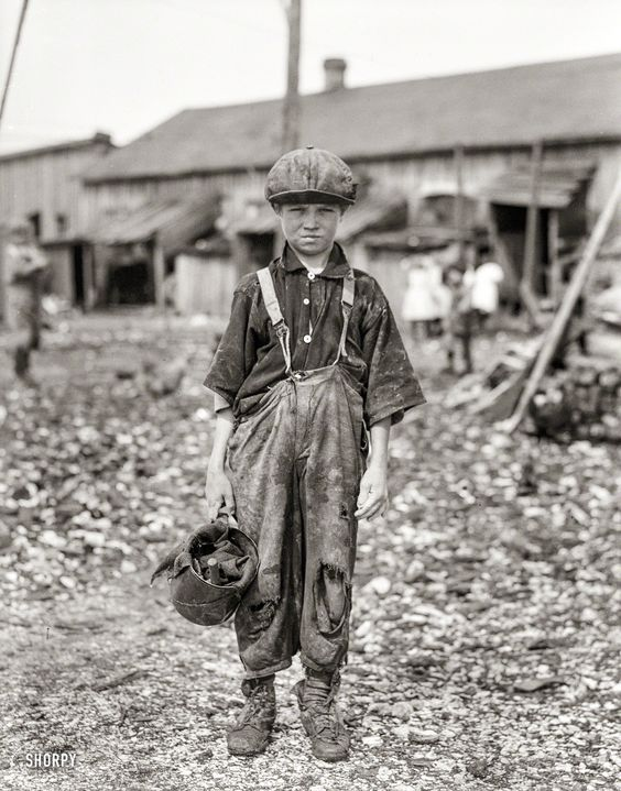 "Raggedy Henry: February 1912. ""Henry, 10-year-old oyster shucker who does five pots of oysters a day. Works before school, after school, and Saturdays. Been working three years. Maggioni Canning Co., Port Royal, South Carolina."" Glass negative by Lewis Wickes Hine:"