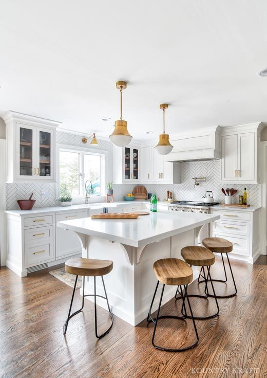 All White Kitchen With Medium Wood Floors And Brass Pendant Lights