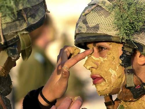 An Israeli soldier putting face paint or mud on another female soldier as they get dressed in camouflage (EPA/IDF).