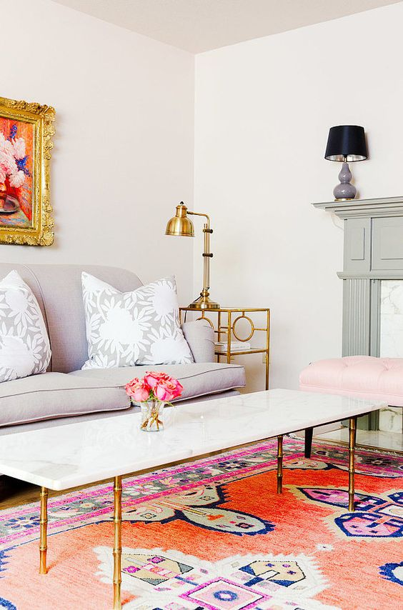 A colorful living room with feminine flair, marble coffee table with gold accents, and Persian rug: