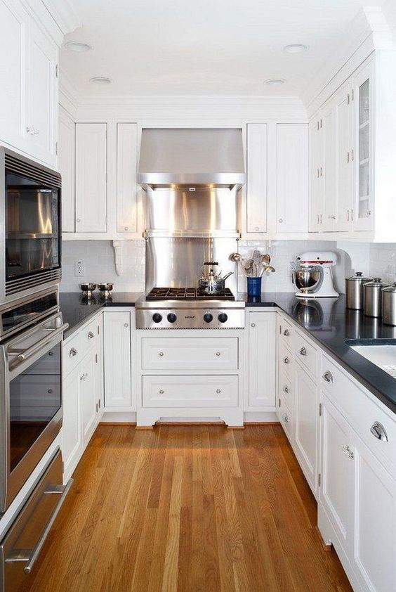 Small classic u-shaped white kitchen with black counters and wood floor. #classickitchen #smallkitchen #ushape #kitchendesign