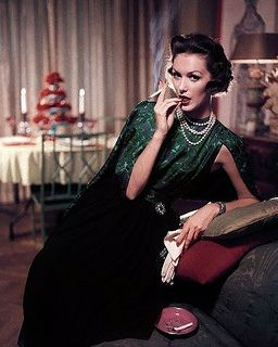Model sporting a green and black floral print dress with matching jacket by Donald Brooks for Danbury, pearls by Marvella, and glitter pin by Albert Weiss (December 1956). #vintage #1950s #fashion #model
