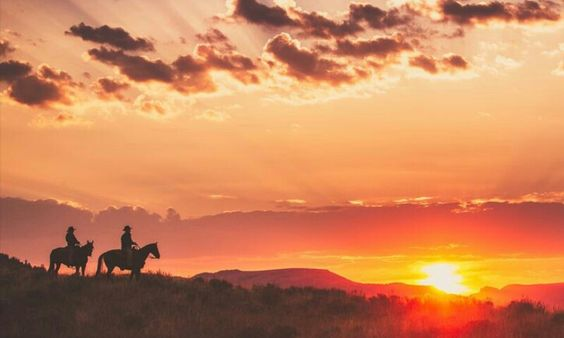 Breathtaking landscape two cowboys riding their horses at the sunset ,beautiful clouds
