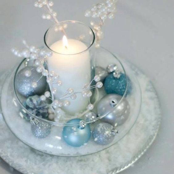 Candle table centre with teal, icy blue, and silver baubles intertwined with crystal garland