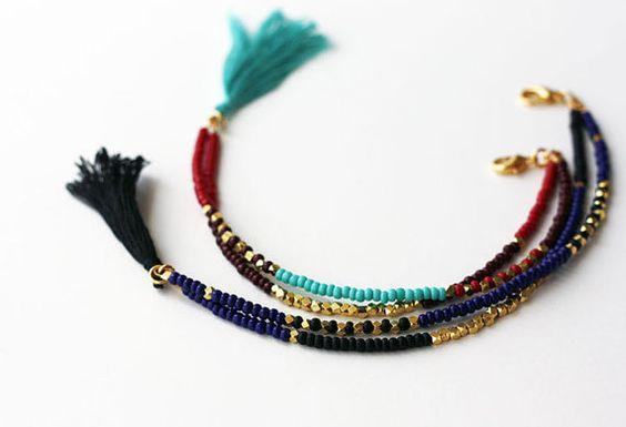 Bracelet Tribal - Friendship Bracelet - Bracelet pompon - Bracelet à Double rang de perles  Cette annonce est pour un bracelet, sil vous plaît choisir un : 1. double brin bracelet en perles dans des couleurs riches de Bordeaux, chocolat, or et turquoise avec un gland en aqua ou, 2. double rang de perles bracelet en bleu marine, noir et or avec un gland en noir.  Détails : -mélange de verre et or plaqué perles de rocaille en laiton, -pompon de broderie de soie, -conclusions de métal, plaqué…