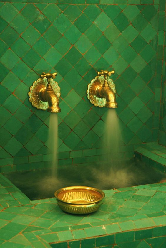 a turkish bath with green tiles and gold-colored brass taps. the color combo is quite pre-raphaelite.:
