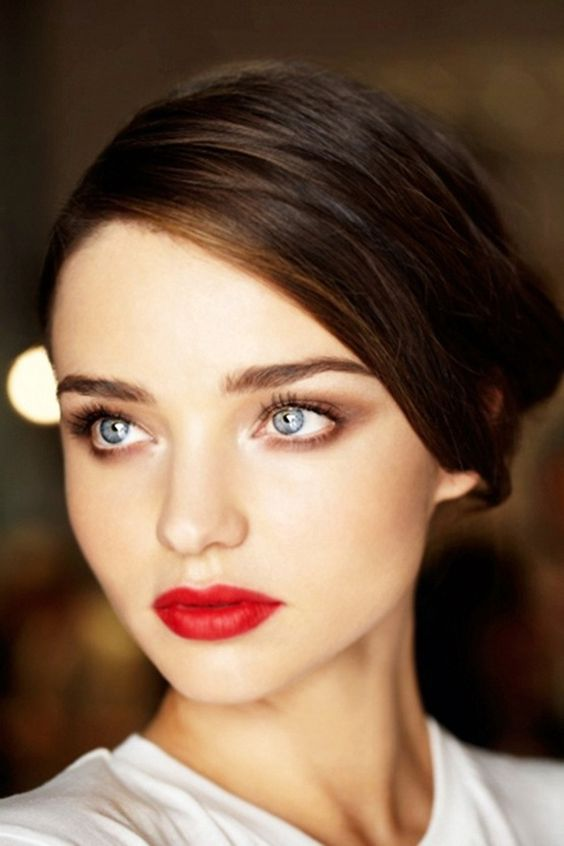 Smokey brown eye makeup.  Red lip. Hair pulled back. A smokey brown eye is much more wearable with a strong lip than darker shadow, but still with impact.