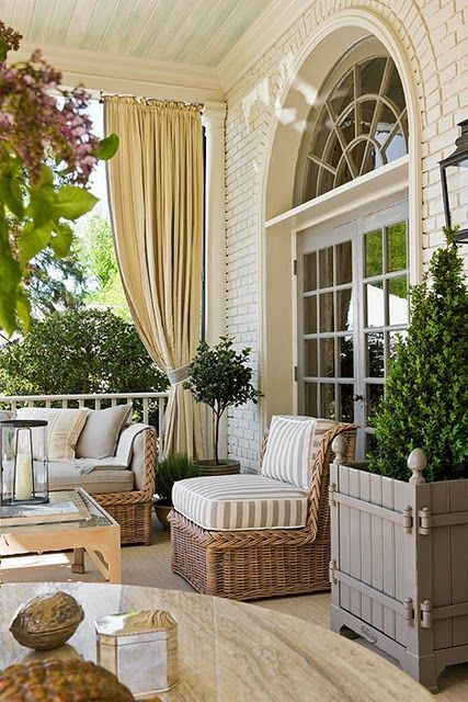 Exterior fabrics, vinyl rugs designed to mimic sisal, and cast iron and stone created an outdoor area as luxurious as the interior. - Traditional Home ® / Photo: Gordon Beall / Design: Andrew Law: