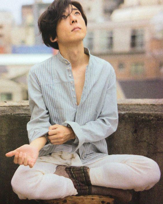 ストライプのシャツを着て座っている高橋一生の画像