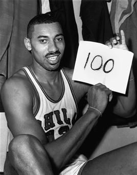 """In this March 2, 1962 file photo, Wilt Chamberlain of the Philadelphia Warriors holds a sign reading """"100"""" after he scored 100 points in a Warriors victory over the New York Knickerbockers. The 100-point performance still remains an NBA record 50 years later."""