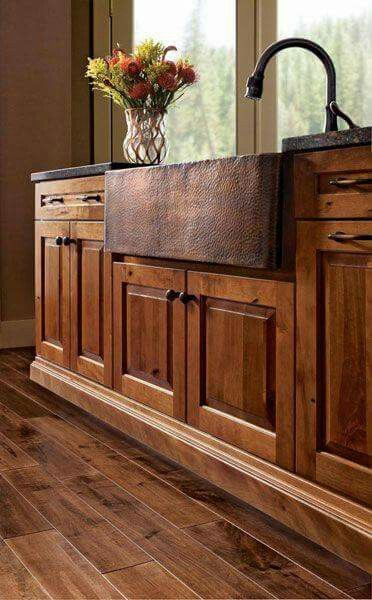 Copper farmhouse sink and beautiful cabinets and floor.
