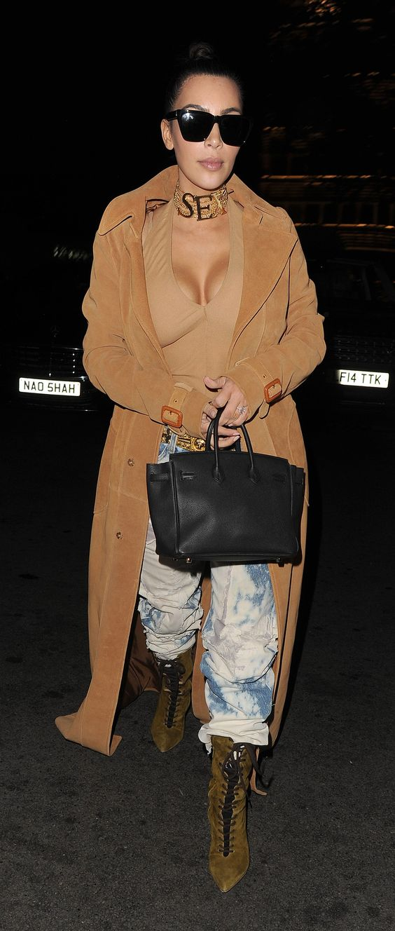 Out in London wearing a nude bodysuit, acid-washed jeans, lace-up suede boots, and a camel duster with her gold Vivienne Westwood 'SEX' choker.