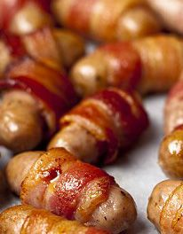 Sausages wrapped in bacon. Traditionally served at Christmas with roast turkey. NOTE: By cocktail sausages, she doesn't mean the kind in a can.