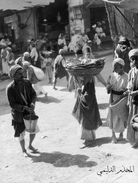صورة تراثية رائعة لاحد اسواق بغداد ويظهر رجل يرش الماء امام محله وكانت هذه طبيعة عامة لاصحاب المحلات وكذلك يظهر طفل يحمل على Arab Culture Baghdad Iraq Baghdad