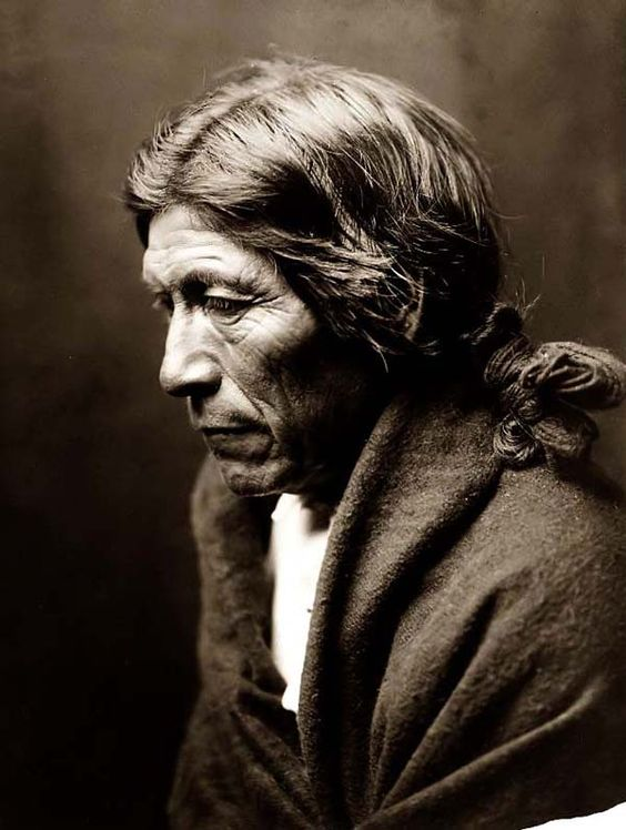 """Pose-a Yew, a Nambe Indian Brave. It was created in 1905 by Edward S. Curtis. The photo illustrates Pose-a ye, or """"Dew Moving"""", Nambe Brave in a head-and-shoulders portrait, facing left."""