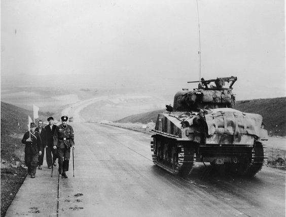 """American tank M4 «Sherman"""" from the 1st U.S. Army travels on the highway in the direction of Kassel past a group of German soldiers surrendering."""