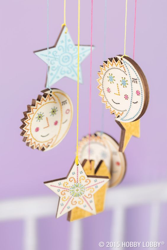 Here's a sweet dream for a little someone: a DIY mobile. Ours features hand-stitched celestial shapes suspended from a painted embroidery hoop. Top: The floss ends are threaded through a wooden spool and sandwiched between two owl cutouts.