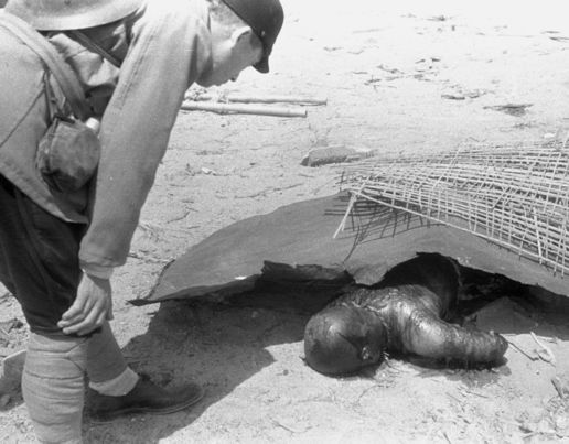 A Japanese Imperial Army investigation team member checks a body of the Hiroshima atomic bomb victim, taken photographed between August 10 to 12, 1945 in Hiroshima, Japan