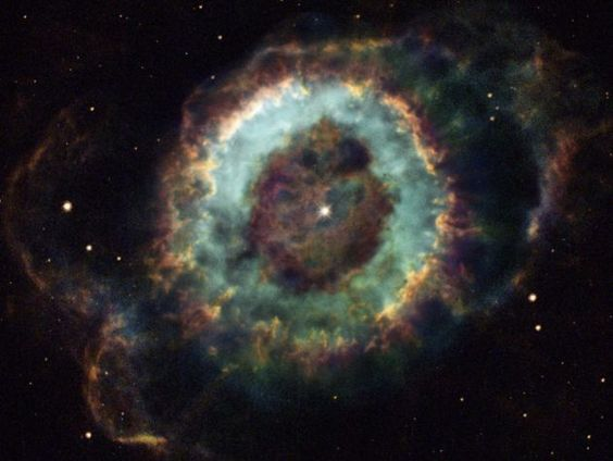 "The Little Ghost Nebula is a planetary nebula. Nothing to do with planets, but they looked like planets in 18th century telescopes.  Planetary nebulae form when a star like the Sun runs out of hydrogen and swells into a red giant, throwing off the outer layers of atmosphere.  This often happens fairly symmetrically.  (Image: Hubble Heritage Team)  ©Mona Evans, ""Nebulae"" http://www.bellaonline.com/articles/art43407.asp"