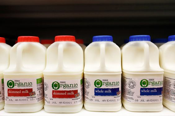 Plastic cartons of organic skimmed milk, left, and whole milk sit displayed for sale. There's a growing body of evidence challenging the notion that low-fat dairy is best.