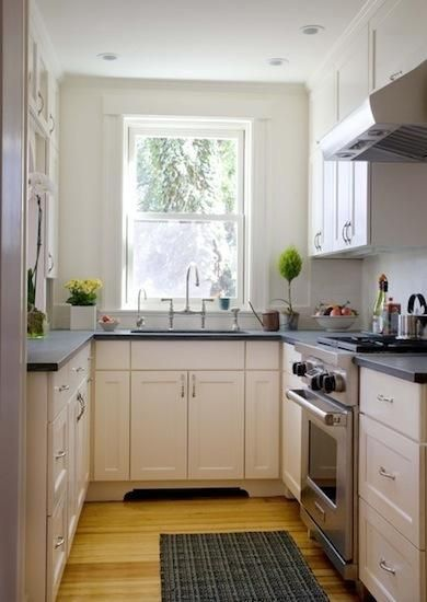 offwhite cabinets to ceiling, wood floor, honed granite or slate counters, stainless appliances & pulls