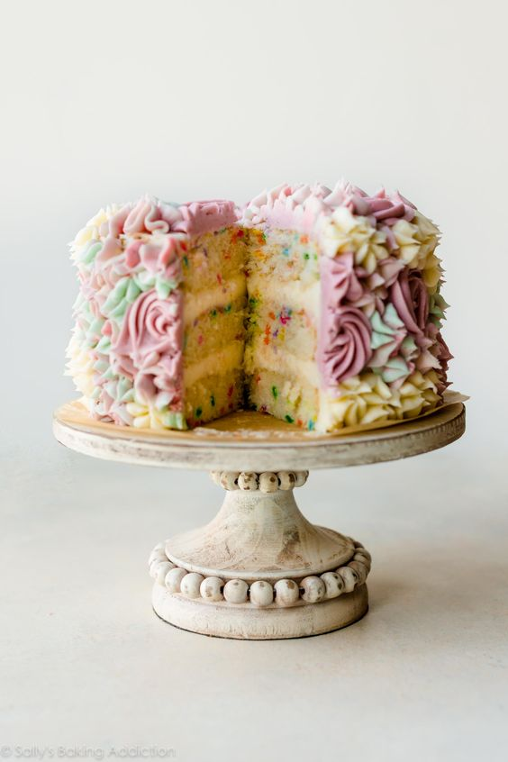 Homemade 6 inch funfetti layer cake is filled with sprinkles and decorated with vanilla buttercream flowers! Find the easy recipe and cake decorating video on sallysbakingaddiction.com
