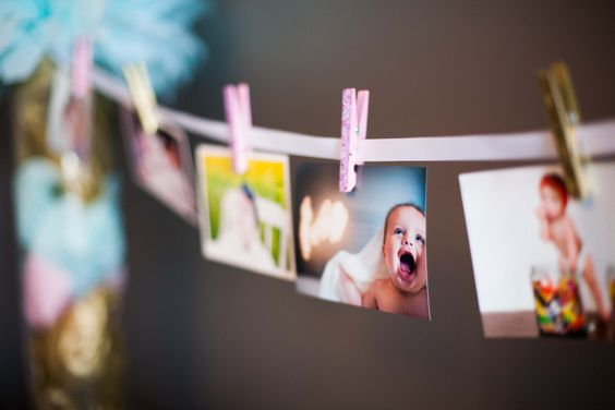 Simple monthly photos banner for first birthday - love the use of ribbon and mini-clothespins! #firstbirthday