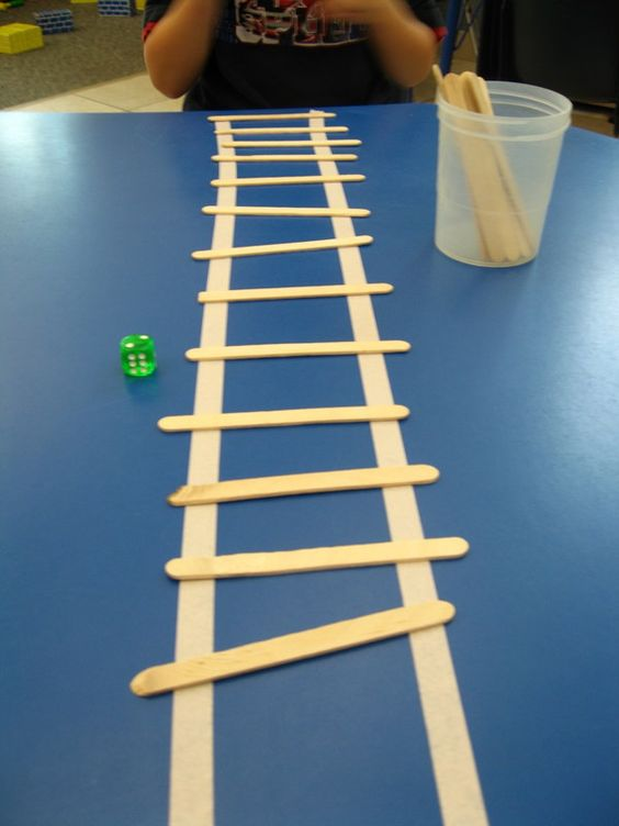 "I did this fun and easy game for unit about fire fighters and construction workers.  Place two long strips of tape up the table and give the kids dice and a cup of popsicle sticks. They roll the dice, count the dots and add the rungs to the ""ladder."":"