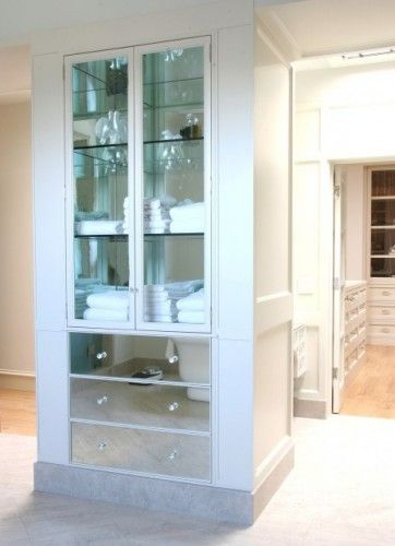 linen closet in the bath with glass cabinet fronts & mirrored drawer fronts