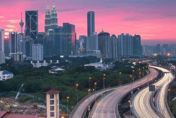 https://flic.kr/p/Cytkga | Kuala Lumpur at Sunset | The horizontal cityscape image of Kuala Lumpur city skyline in the evening after thunderstorm with colorful sky and traffic light trail in the expressway leading into the city. Petronas or Twins Towers is illuminated with light up.