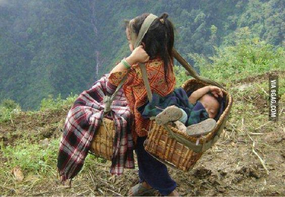 Girl carrying her brother - Nepal