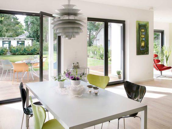 Stühle in unterschiedlichen grüntönen lassen den schlicht gestalteten Essbereich interessanter wirken.