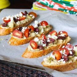 Greek Bruschetta, made with hummus, kalamata olives, cherry tomatoes, artichoke hearts & feta cheese.