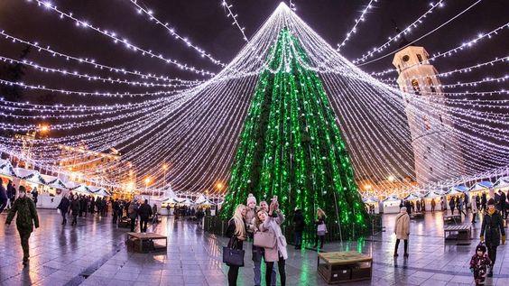 Los visitantes se toman fotografías delante del árbol de navidad iluminado en la plaza de la catedral en Vilnius, Lituania.