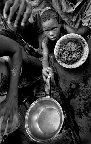 Clayson Menthor, 13, holds out a small pot for some beans and rice provided by a church outside of Cabaret