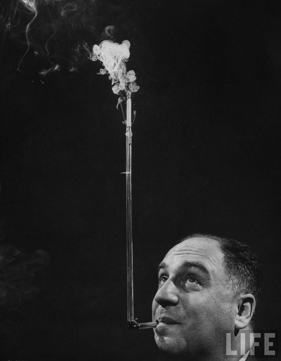 President of Zeus Corp., Robert L. Stern, smoking cigarettes from his self-designed periscope cigarette holder . US . March 1954 . Photo by Yale Joel: