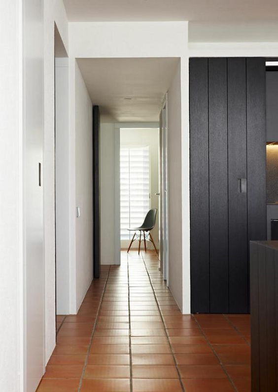 Square edge terracotta tile contrasting with dark modern joinery. Minimalist furnishings, monochrome colour palette: