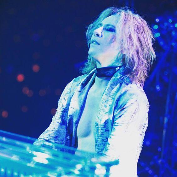 青いライトの中でピアノを弾いているXJAPAN・YOSHIKIの画像