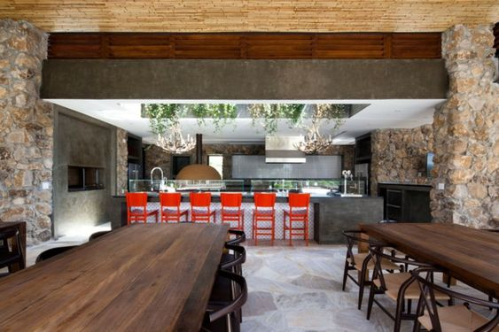 coole Küche gestalten Stein Wand Kochinsel rote Barhocker
