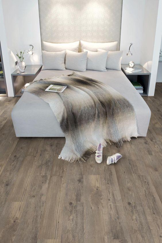 Slaapkamer in natuurlijke kleuren. De kop van het bed past samen met de nachtkastjes precies tussen de wandjes aan weerszijde en geeft de slaapkamer een bijzondere look. Met de extra kussens en het kleed op bed straalt de slaapkamer luxe uit. De PVC vloer met houtmotief is nauwelijks van een echte houten vloer te onderscheiden. De vloer komt uit de Authentic Plank collectie van mFLOR. mFLOR