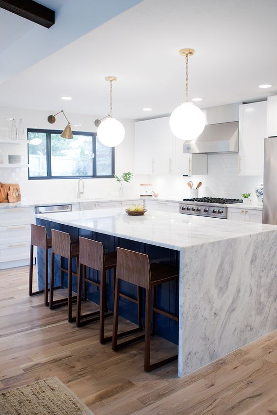 A kitchen reveal for a mid-century modern remodel. White cabinets, navy island, and brass hardware.: