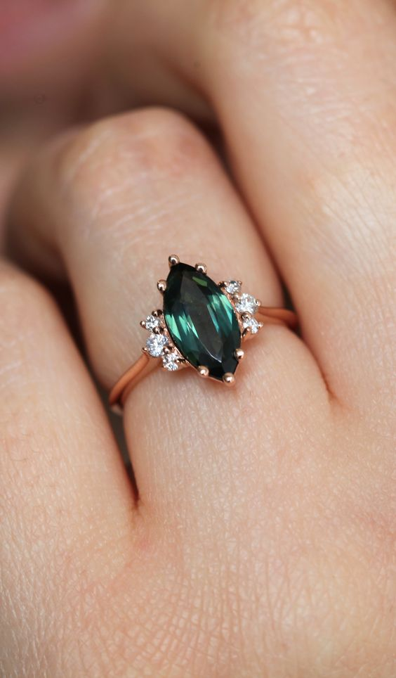 A delicate marquise engagement ring features 1.5ct gorgeous natural emerald with side diamonds. A beautiful genuine emerald complimented with diamonds to create a simple yet stunning ring. The design can be made with gemstones of your choosing. If you would prefer a custom ring, please contact us before purchase.